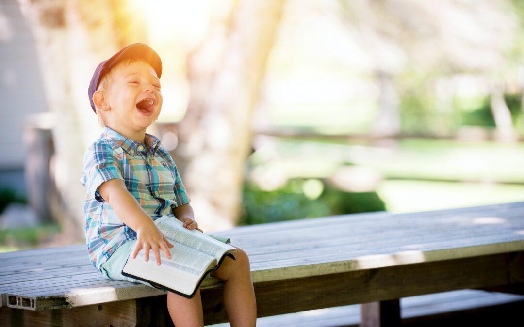 Lapsi istuu ja lukee kirjaa nauraen